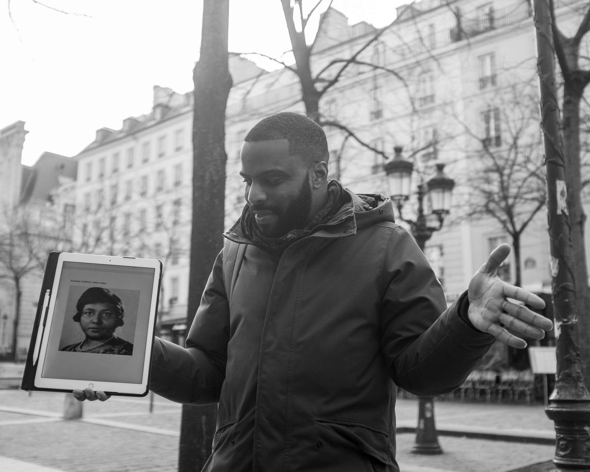 Black and white photograph of Kévi Donat. He's standing across the street from an old building, presumably in Paris, and he's facing the camera with arms outstretched. In his right hand is a tablet with the picture of a Black woman. He's looking down at the tablet.