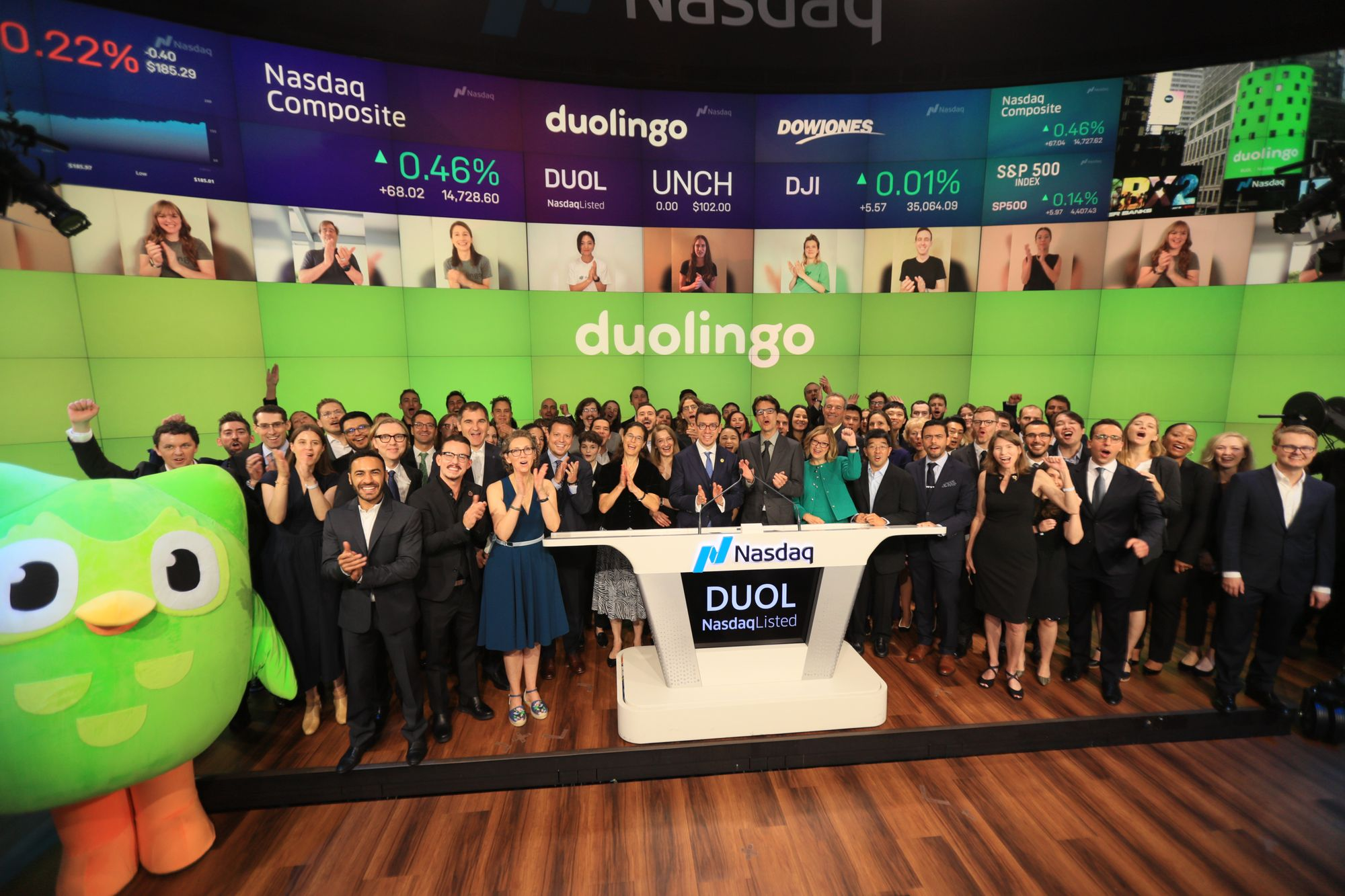 """photogrpah of blog post author and Duolingo co-founder and CEO, Luis von Ahn, standing with a group of ~100 Duolingo employees and the green Duolingo owl mascot at the Nasdaq podium which is labeled """"DUOL""""."""