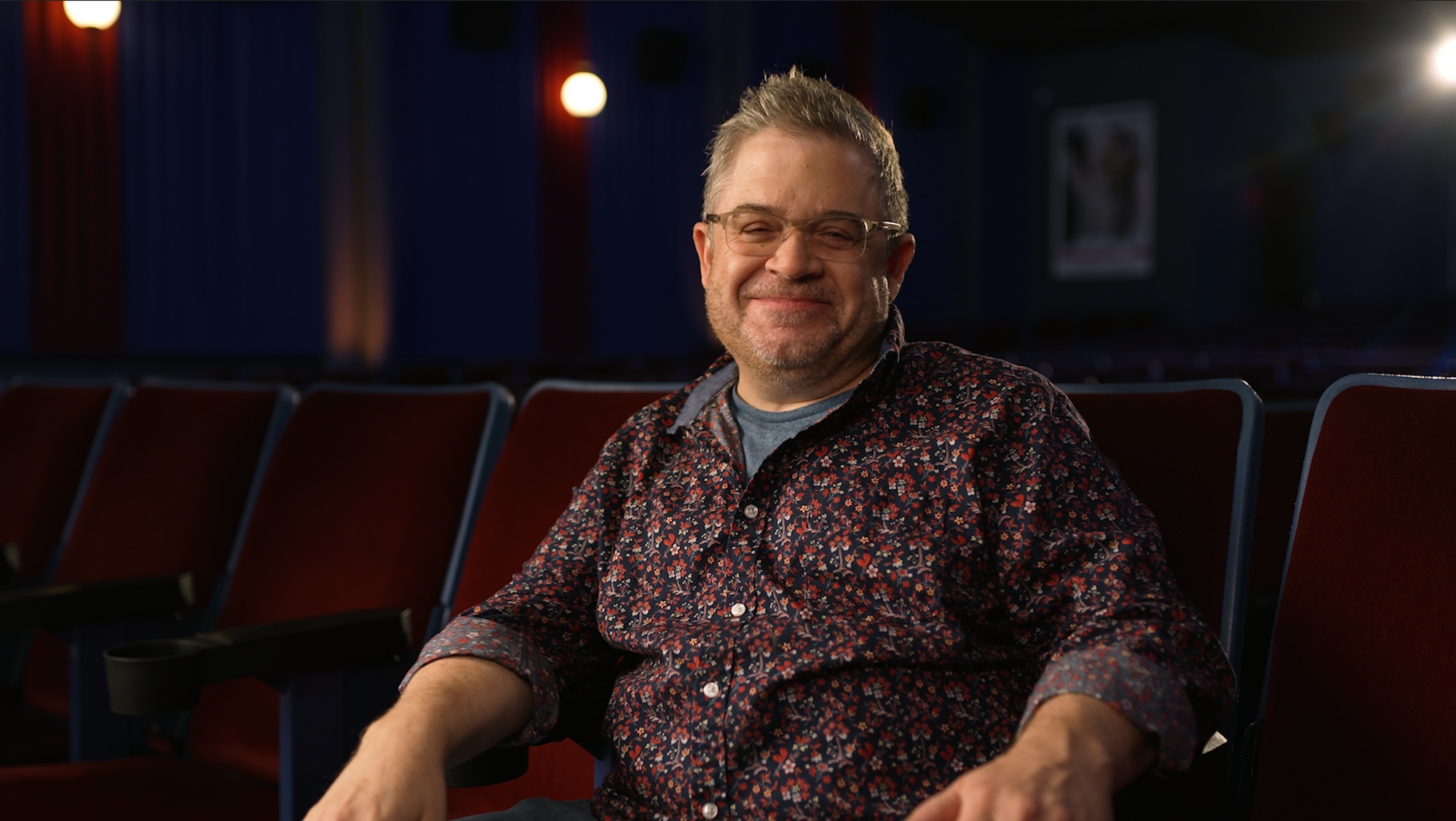 photograph of Patton Oswalt sitting in a movie theater alone