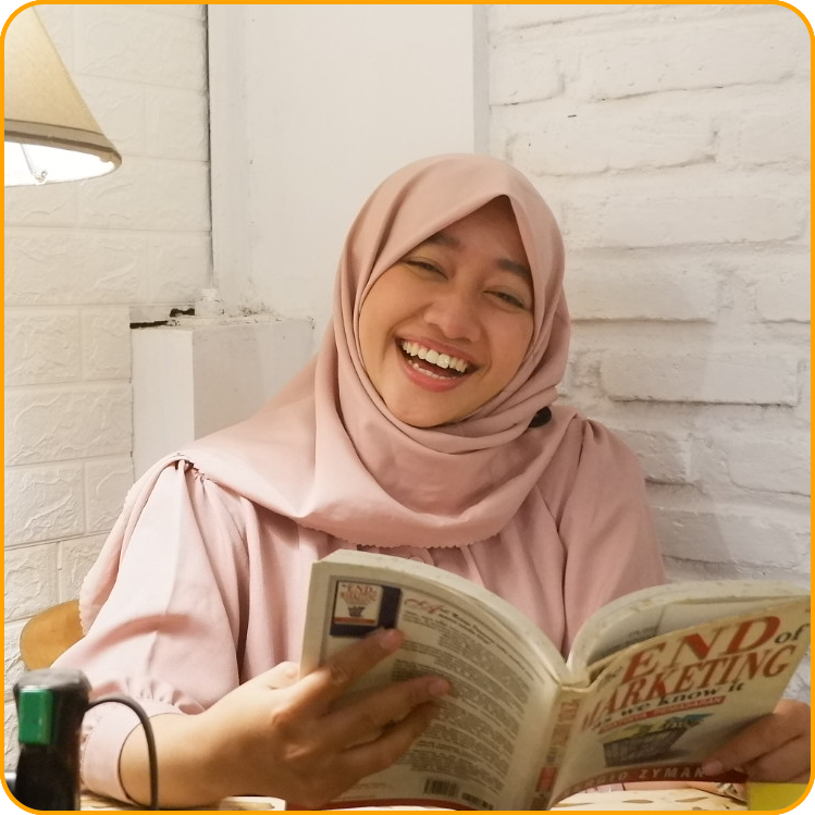 Dwi, a student from Indonesia, smiles while reading a book in her flat