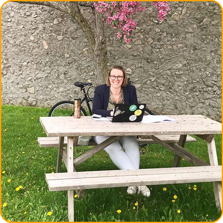 Eva-Maria, a student from Austria, takes a break outside, sitting at a picnic table under a pink flowering tree.