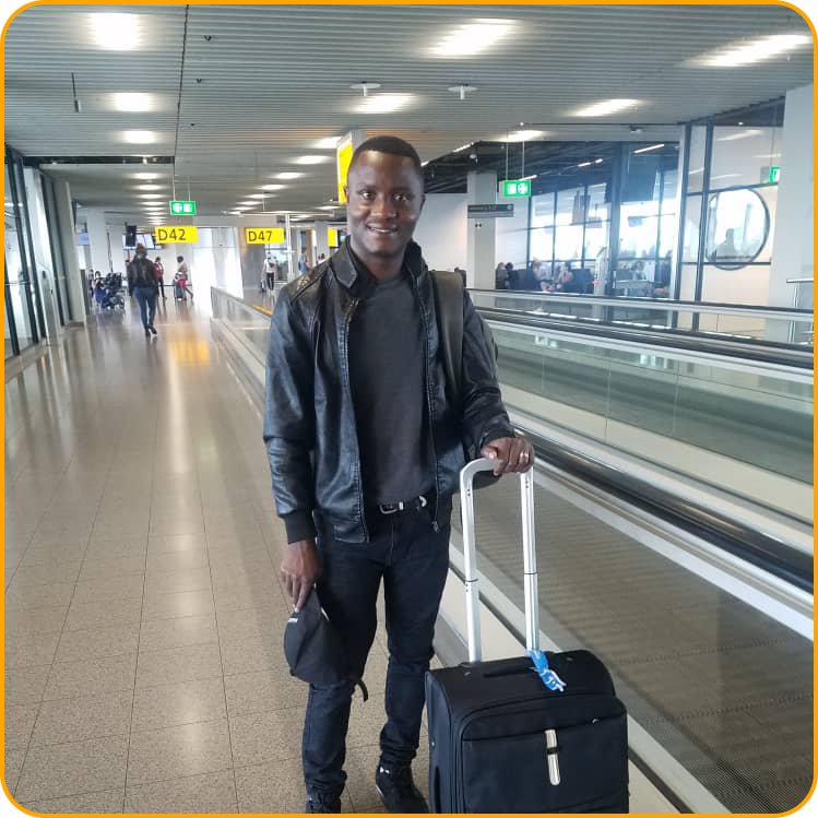 Philbert, a student from Rwanda, is smiling with a suitcase in the airport as he arrives in Ireland to study abroad.