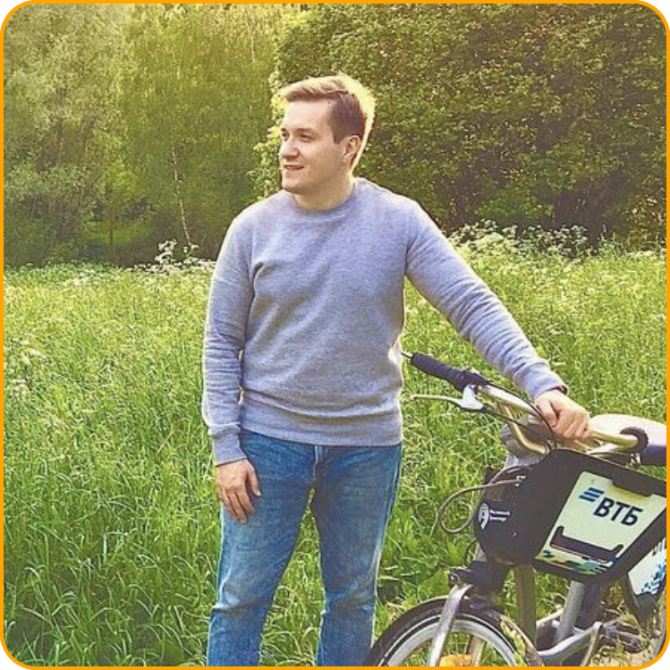 Picture of Sergey standing in a green field with tall grass next to a bicycle